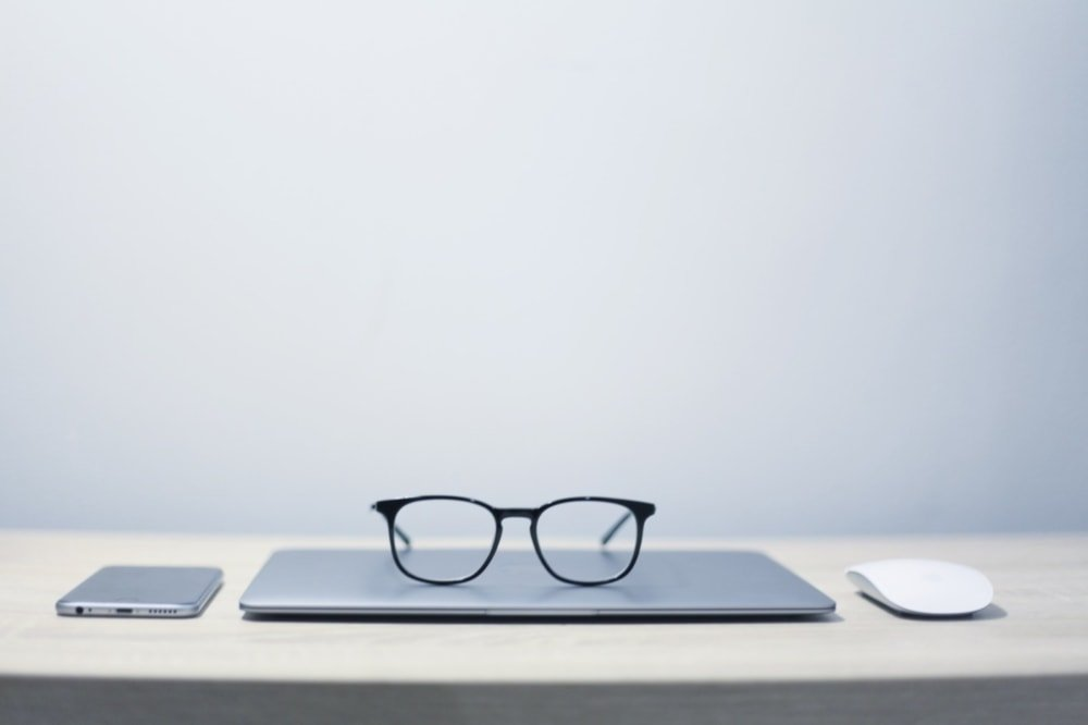 glasses sitting on laptop question with smartphone and mouse on table