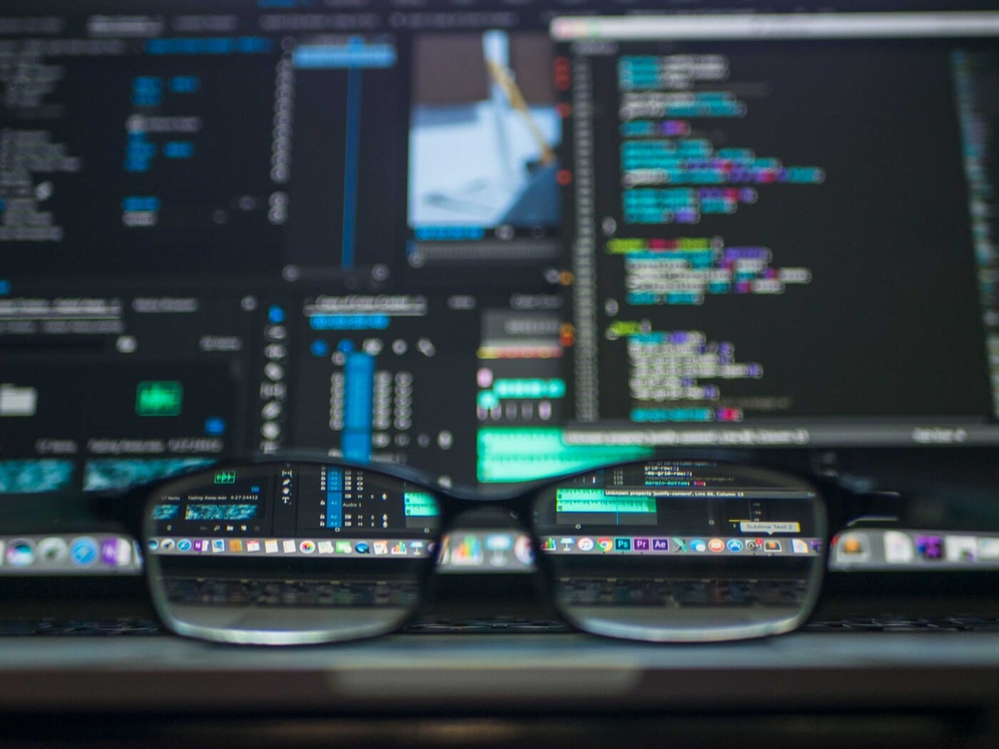 glasses sitting in front of computer monitors with code