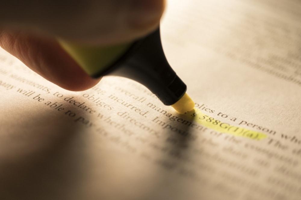 person using highlighter to highlight portion of legislation