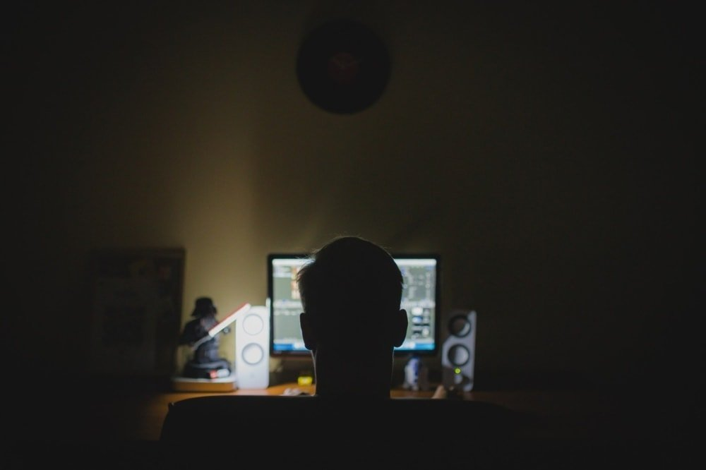 hacker sitting in dark in front of computer screen