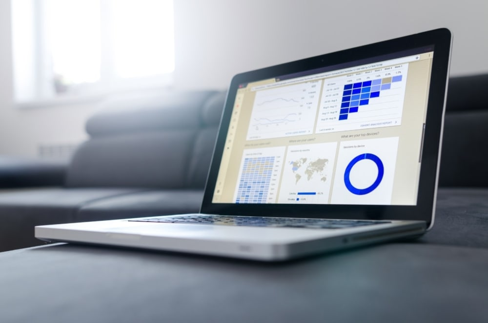 laptop on desk displaying analytic data and graphs