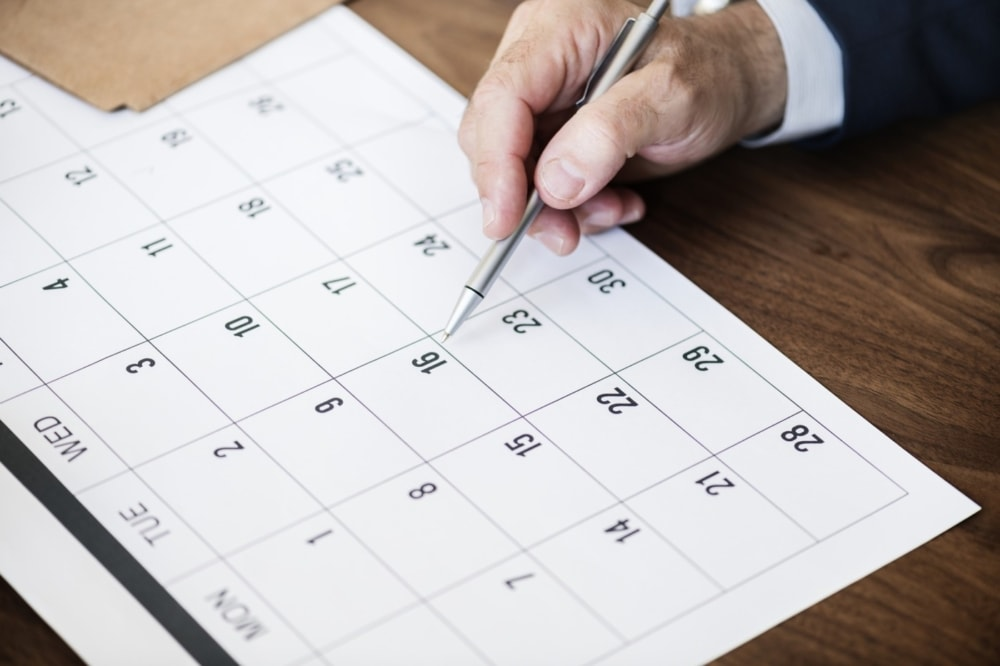 desktop calendar with man writing on one of the dates with an ink pen